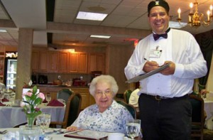 Happy senior woman and server in dining room