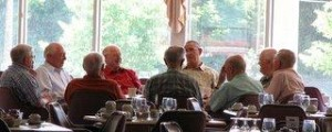 Happy senior men eating together after their retirement home worked to improve mealtimes.