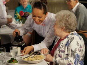 A cheerful young server pours coffee and chats with a happy resident