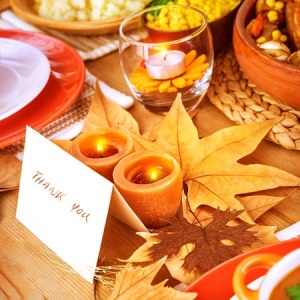 Beautifully decorated Thanksgiving table with thank you card next to place sitting
